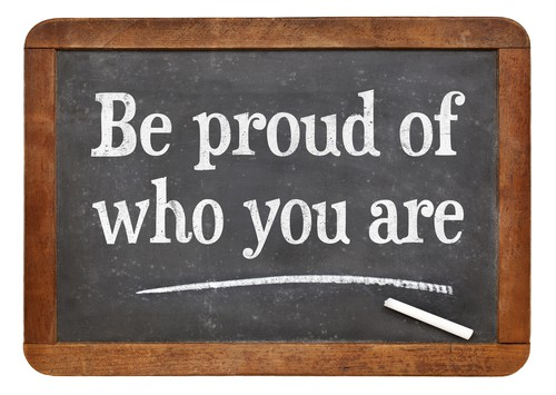 Be proud of who you are - white chalk text on a vintage slate blackboard